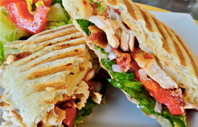 chicken panini topped with tomatoes, lettice and cheese