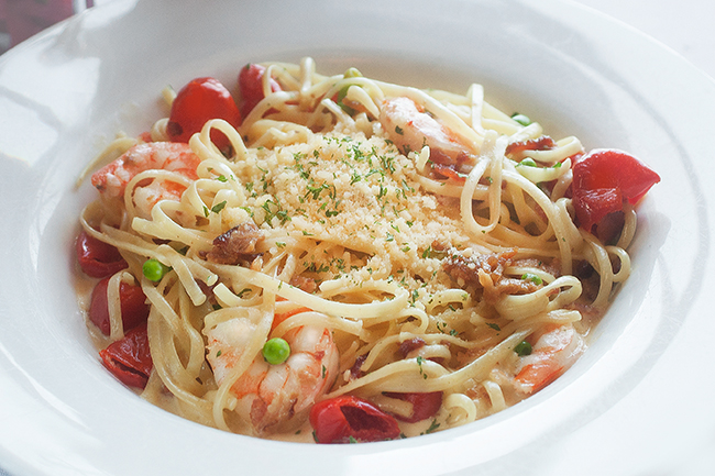 Spaghetti with shrimp, peas, cherry tomatoes and grated cheese