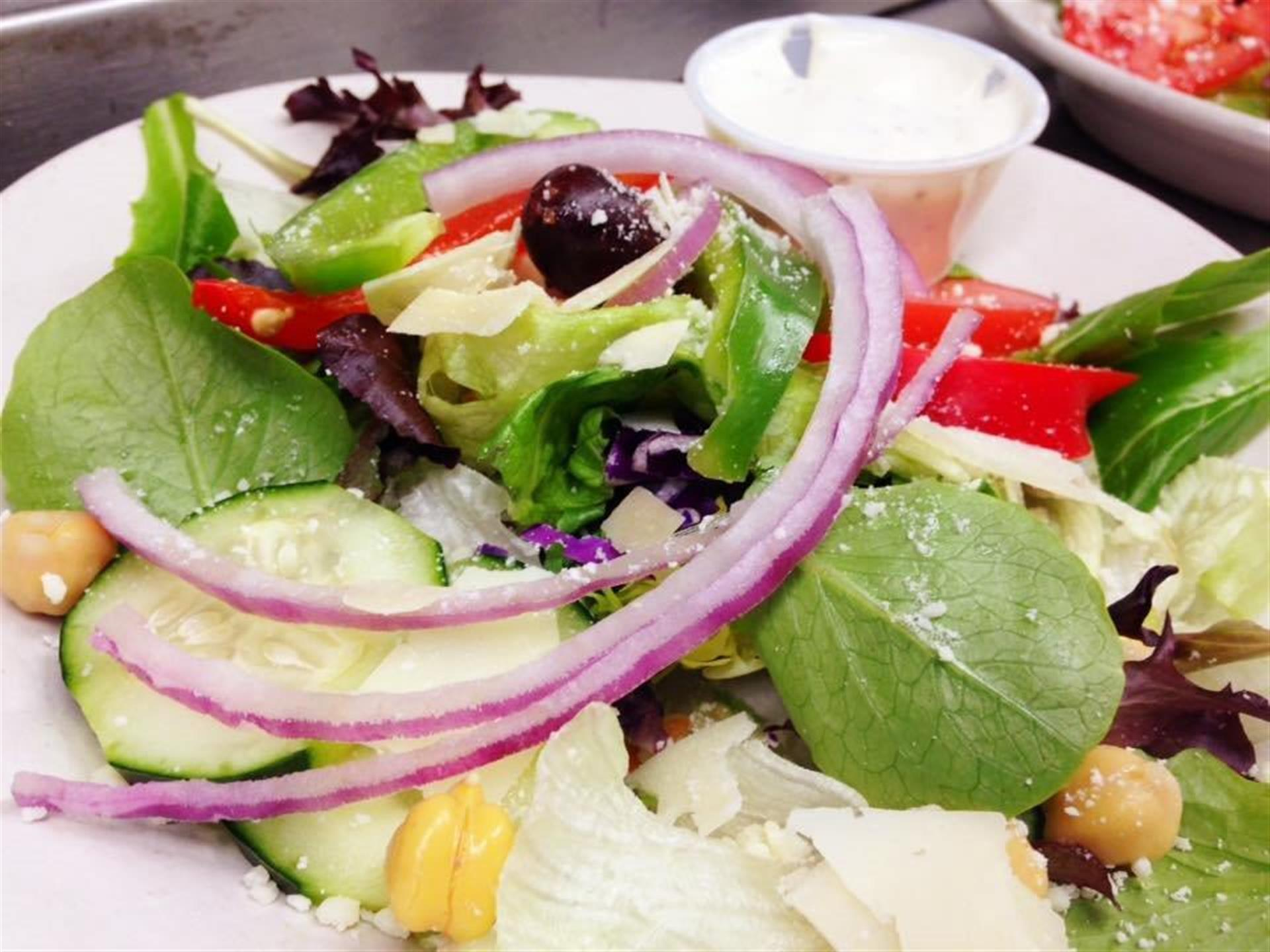 House Salad with mixed greens, olives, cheese, onion, and cucumber tossed in a vinaigarette dressing