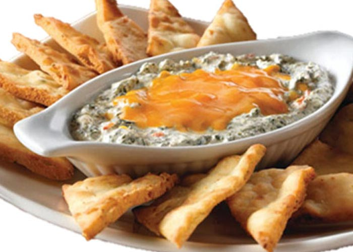 spinach and artichoke dip with melted cheese on top served with homemade pita chips