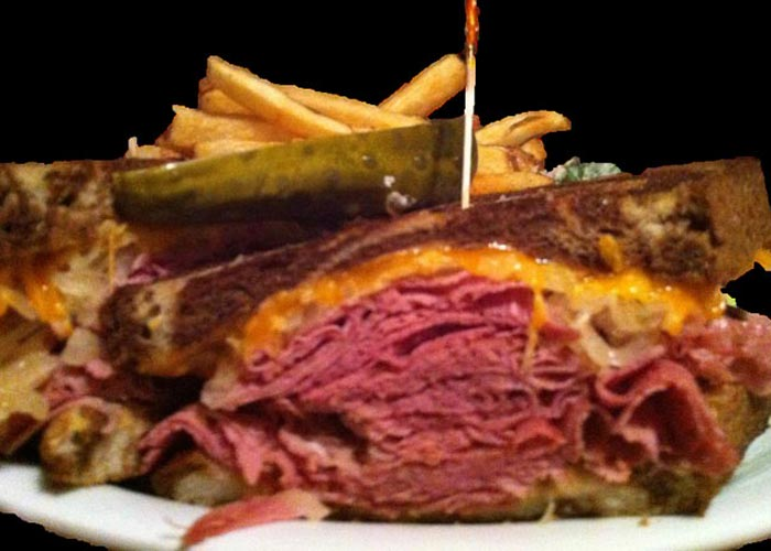 reuben sanwich with pickle and fries