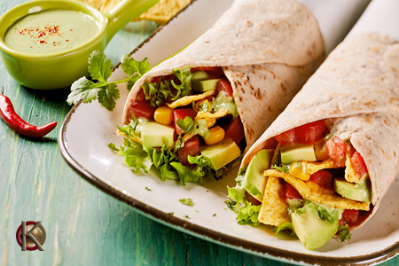 two wraps on a plate stuffed with lettuce, tomato, cuccumber, corn, cheese with dipping sauce on the side.