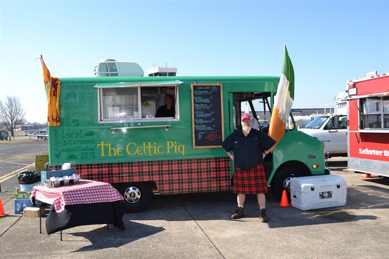 The Celtic Pig's food truck getting ready for service with the head chef standing next to it.