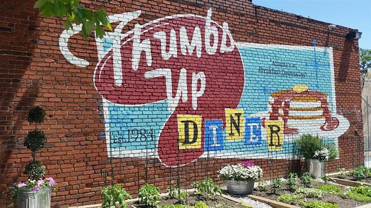 thumbs up diner logo graffiti on the side of a brick building