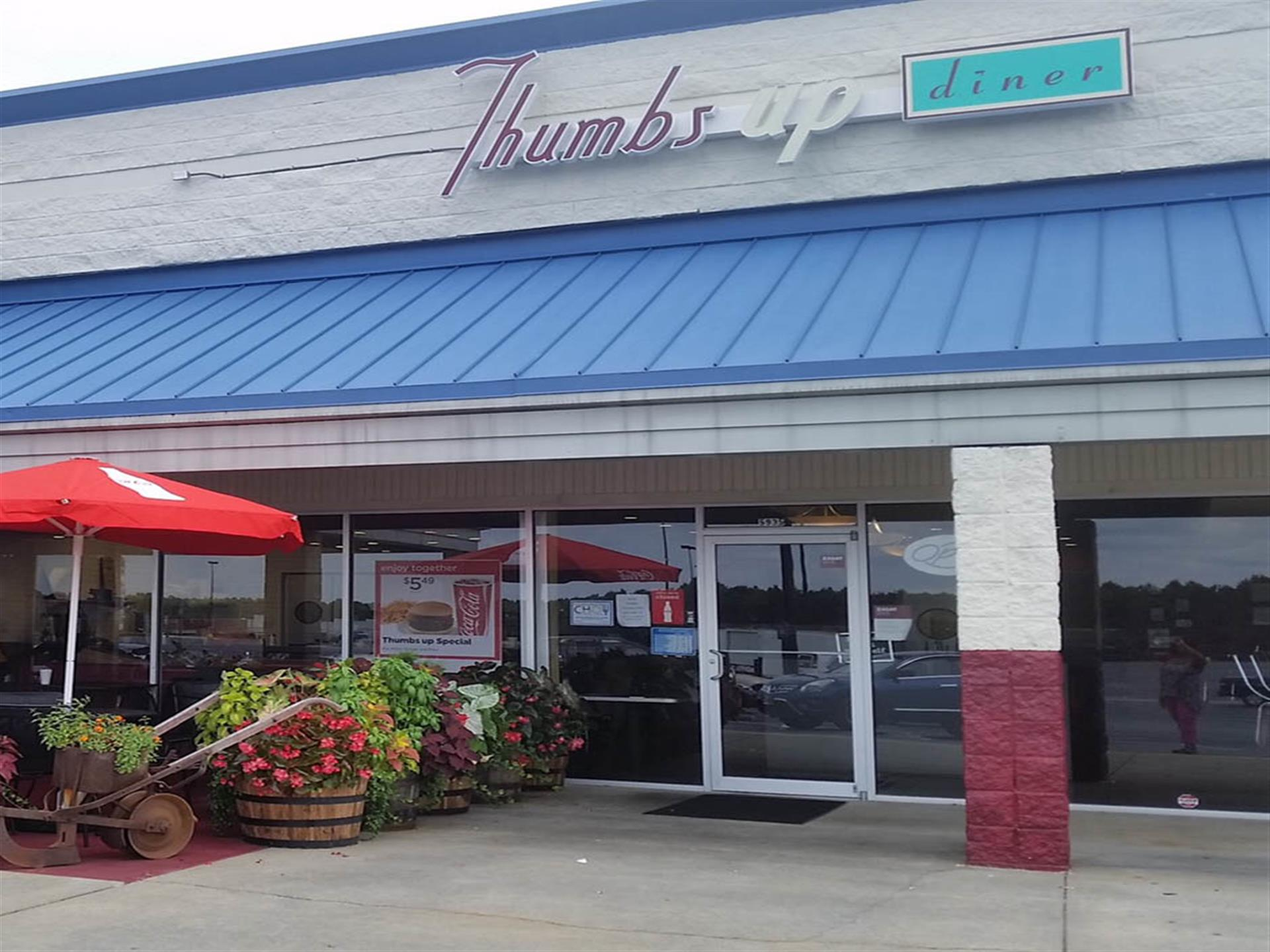 one of the thumbs up diner locations front entrance with an awning and tables setup outdoors