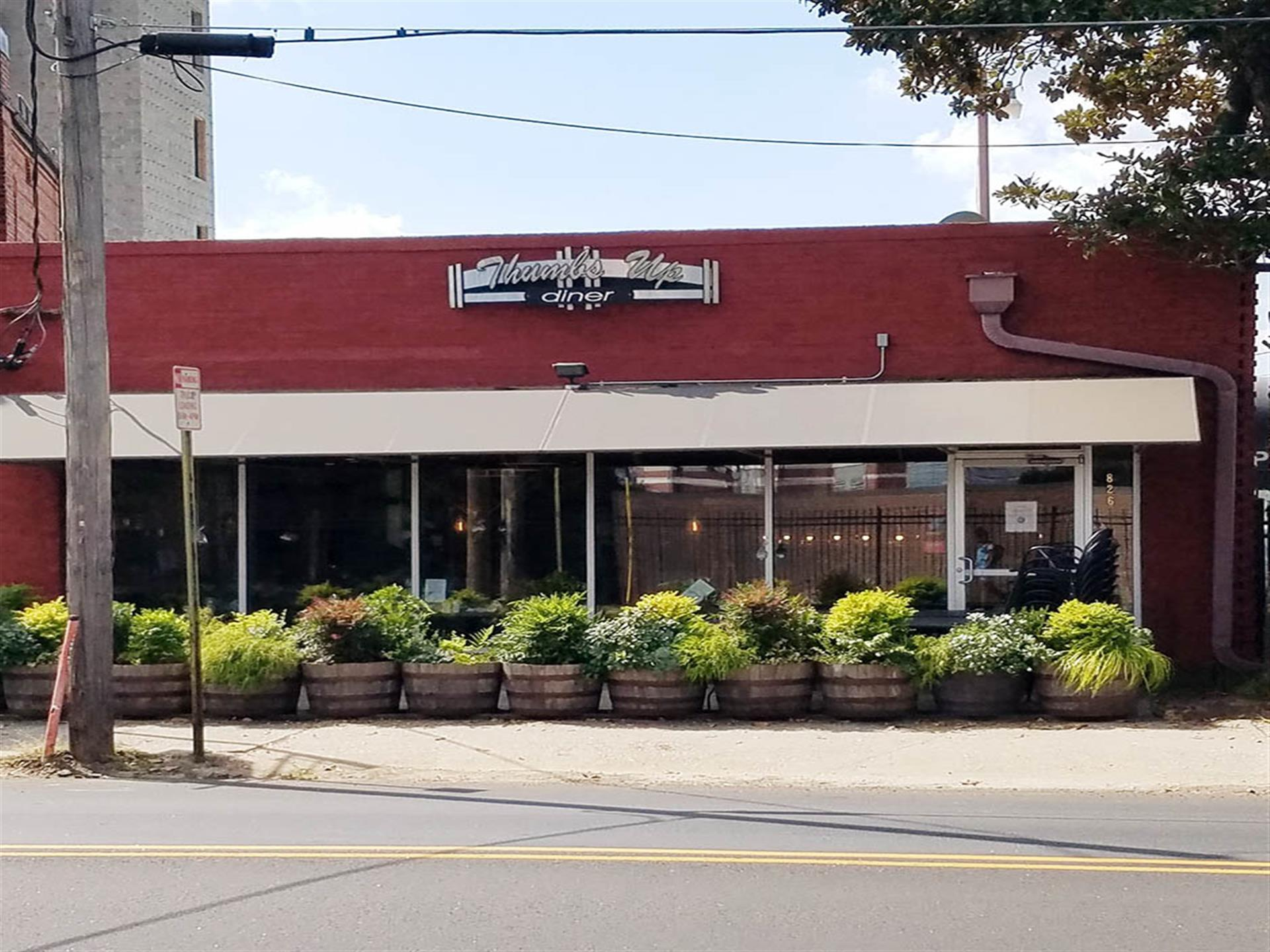 one of the thumbs up diner locations front entrance with brick textures and potted plants