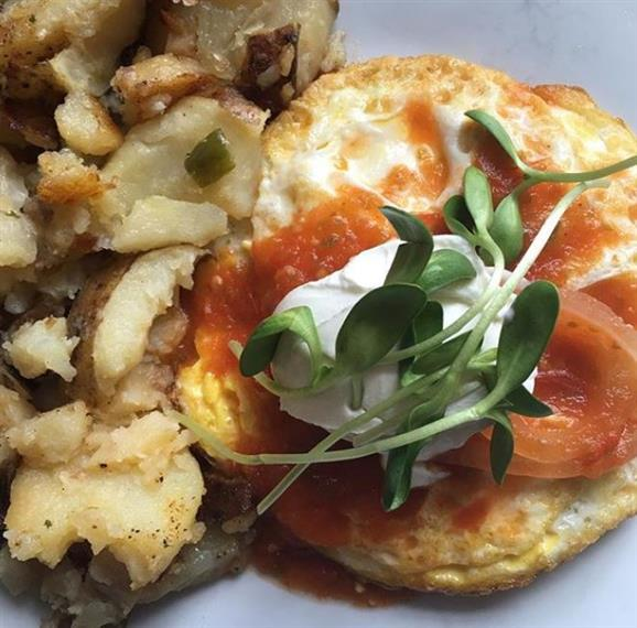 huevos rancheros with breakfast potatoes and microgreens