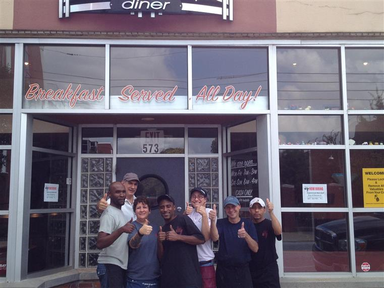 six staff members holding their thumbs up outside the front of thumbs up diner