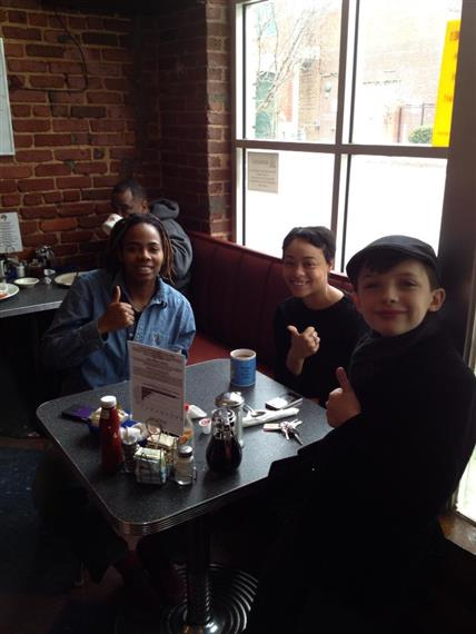 happy family with thumbs up sitting at table by window inside thumbs up diner