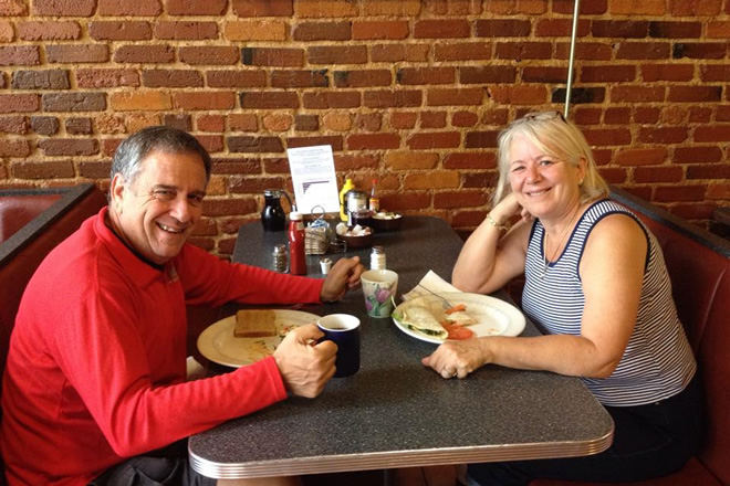 happy couple sitting at a booth inside thumbs up diner eating their breakfast smiling