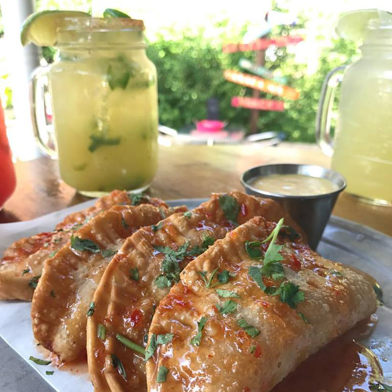 Empanadas on a plate with a margarita in a jar
