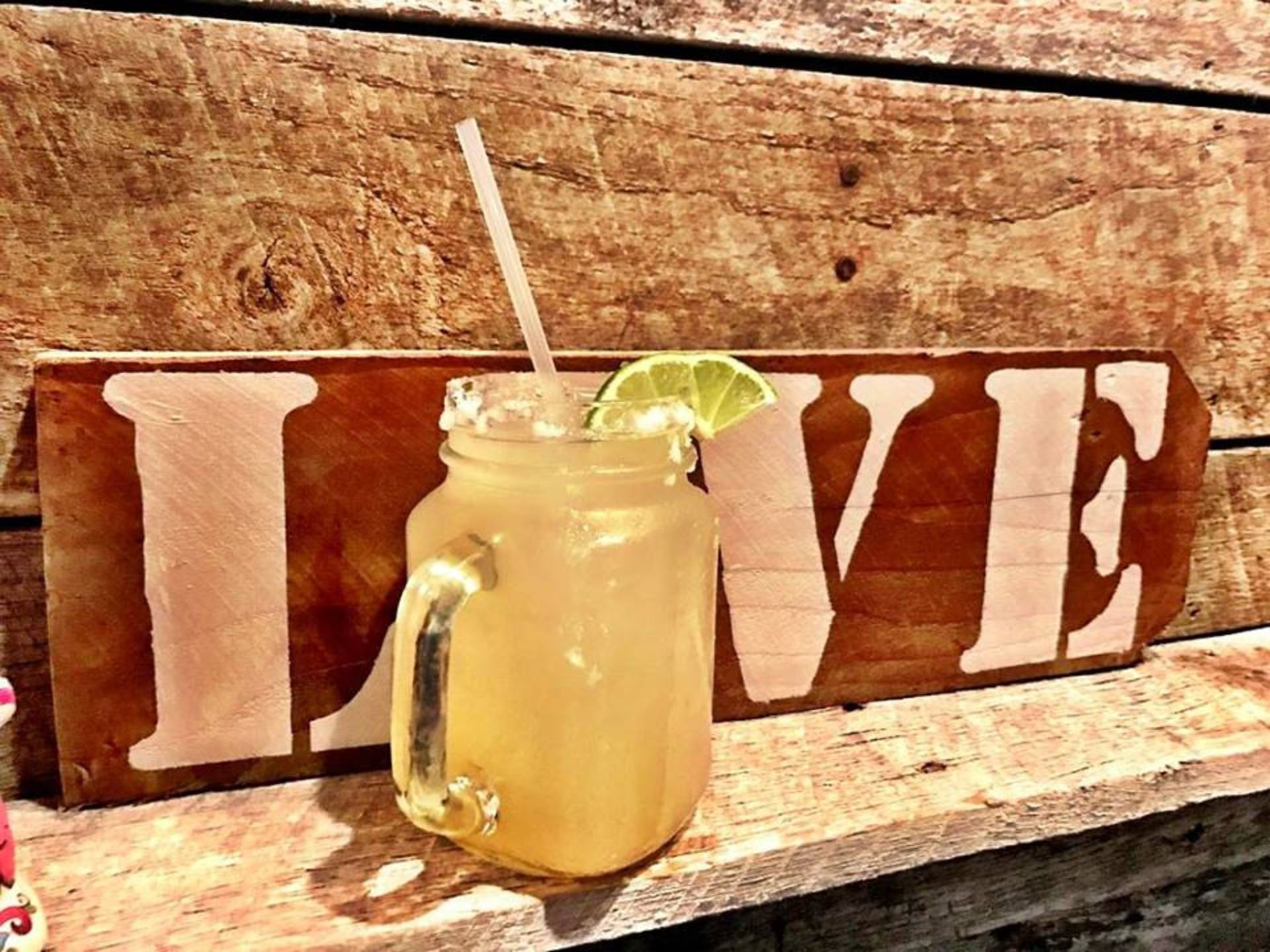 Margarita with a lime and salted rim on a wood shelf beside a love sign
