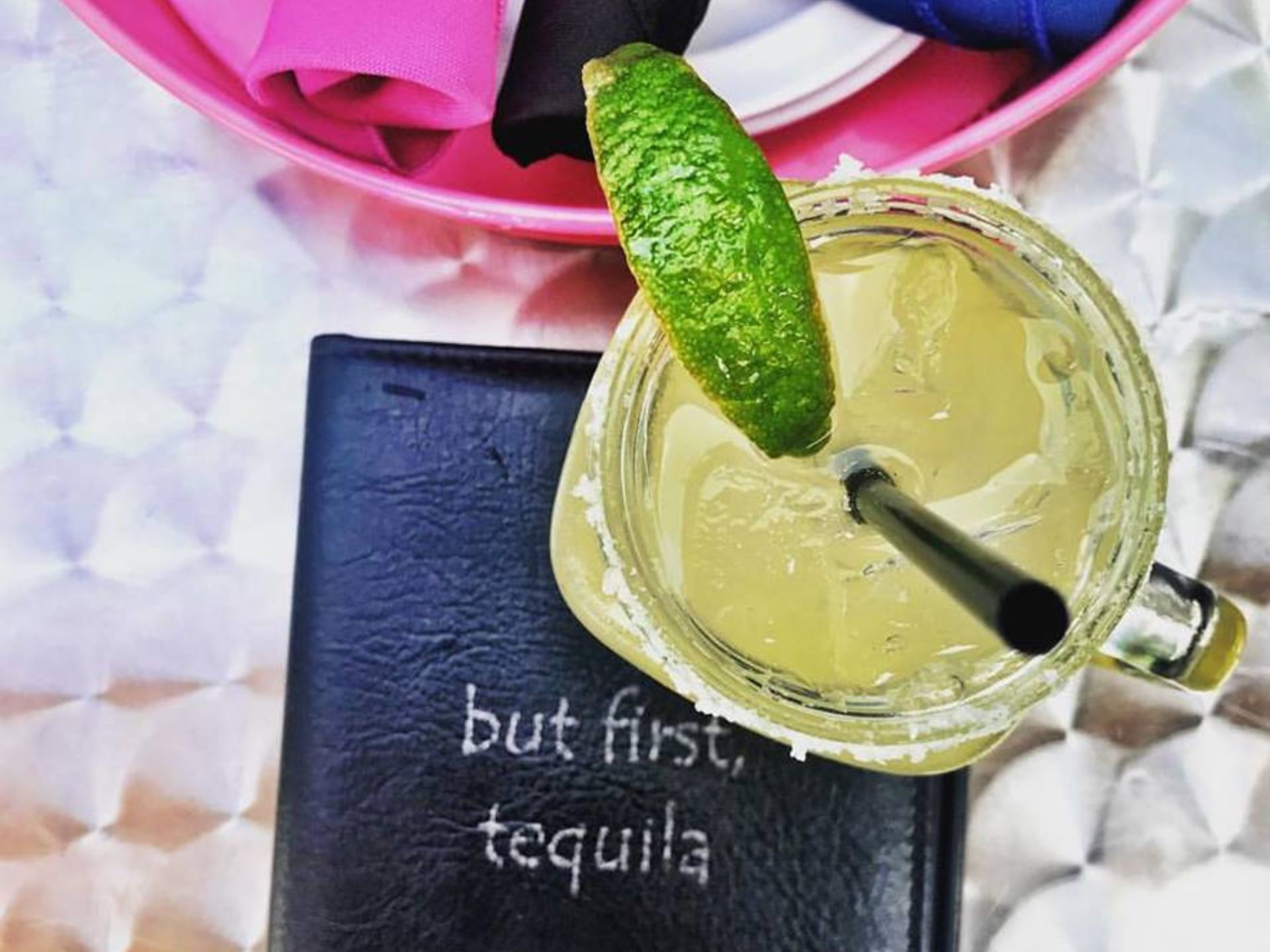 Margarita with a lime and salted rim on top of a check book