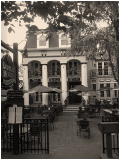 Old style photo of the exterior of The Dublin House and the patio area with tables, chairs and umbrellas