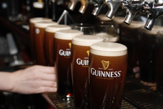 guinness glasses  filled to the brim lined up underneath taps