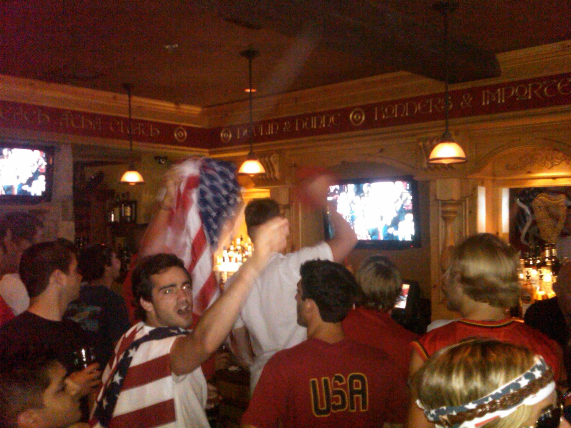 customers in soccer jerseys and american flags cheering at the game