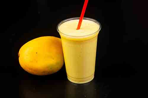 Mango shake next to whole mango