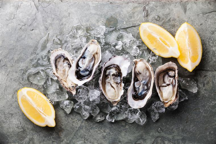 oysters on the half shell on ice with lemon wedges