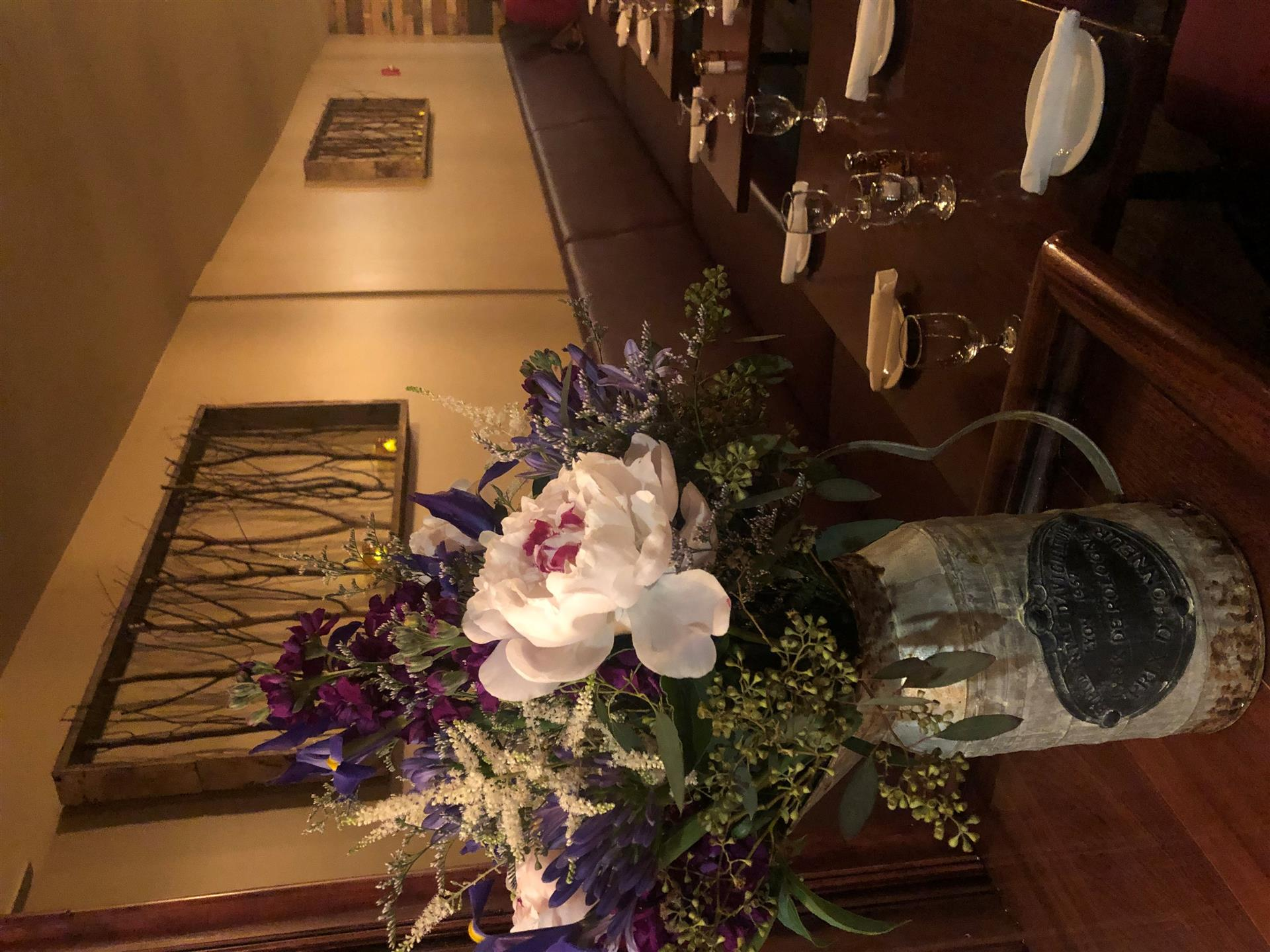 4 tables set with a metal jar with purple and pink flowers in it