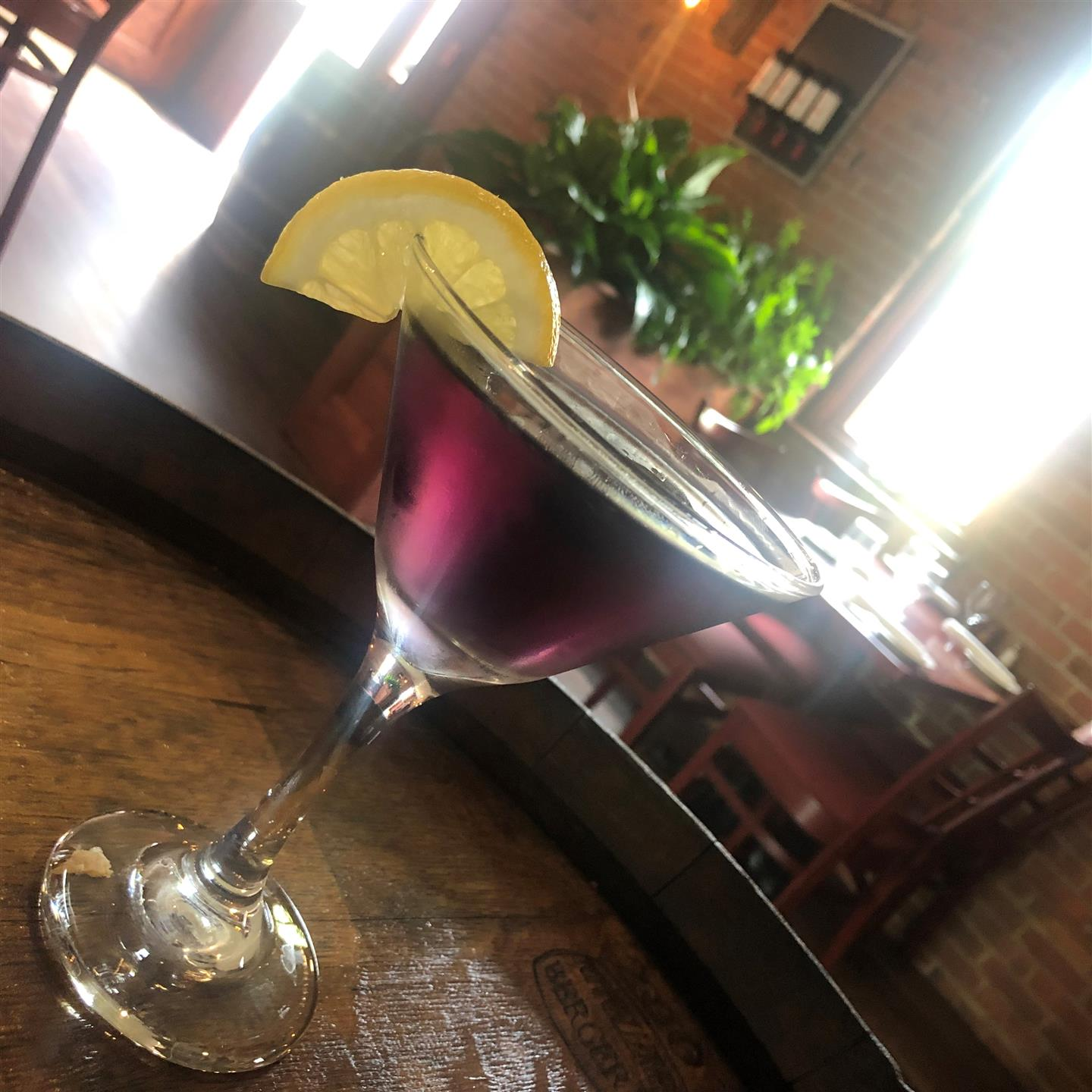 a purple cocktail with a lemon wedge