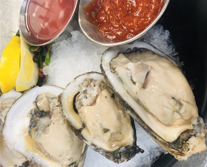raw oysters over ice with lemon wedges and cocktail sauce on side