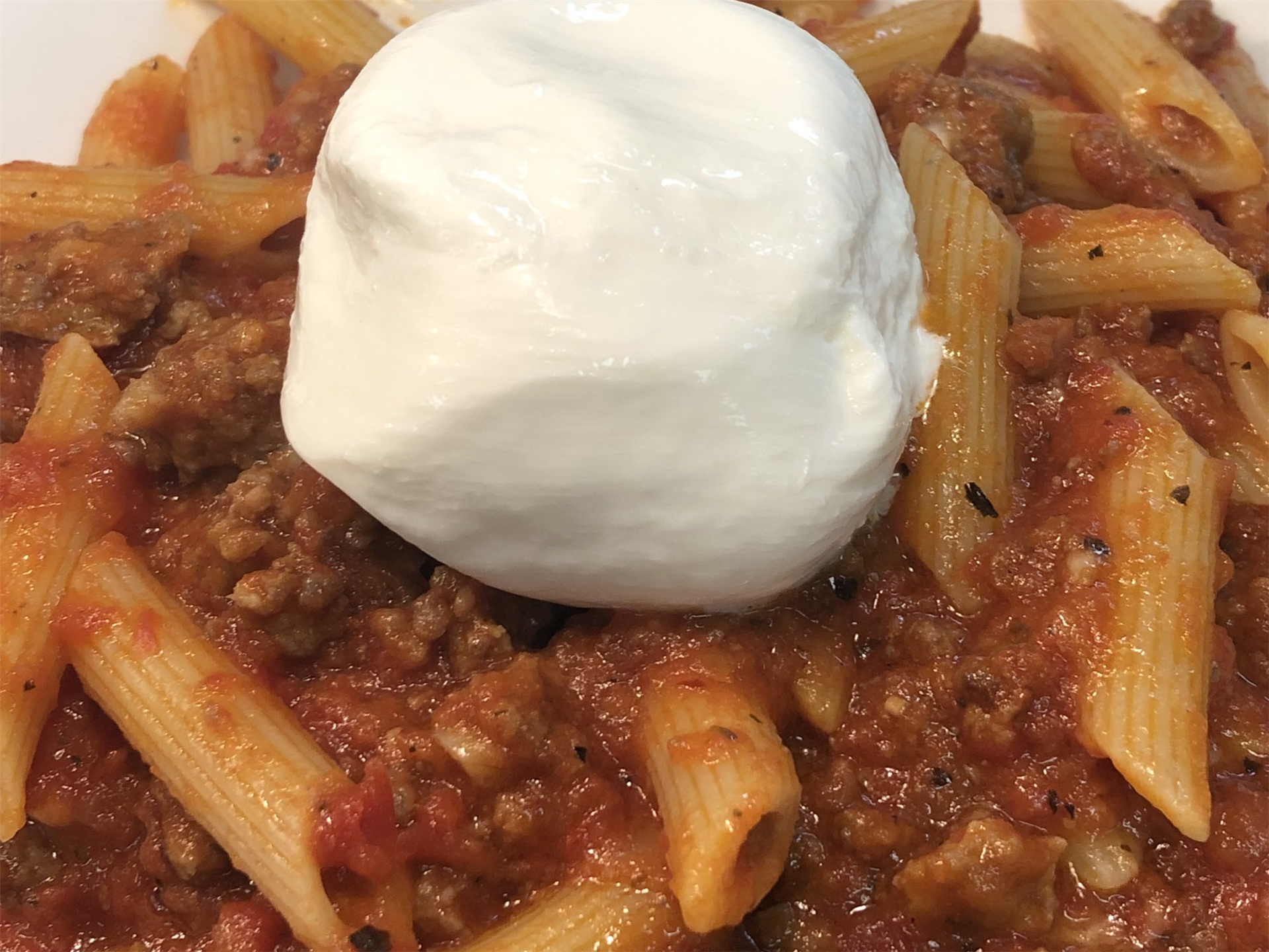 pasta with meat sauce and a dollop of sour cream