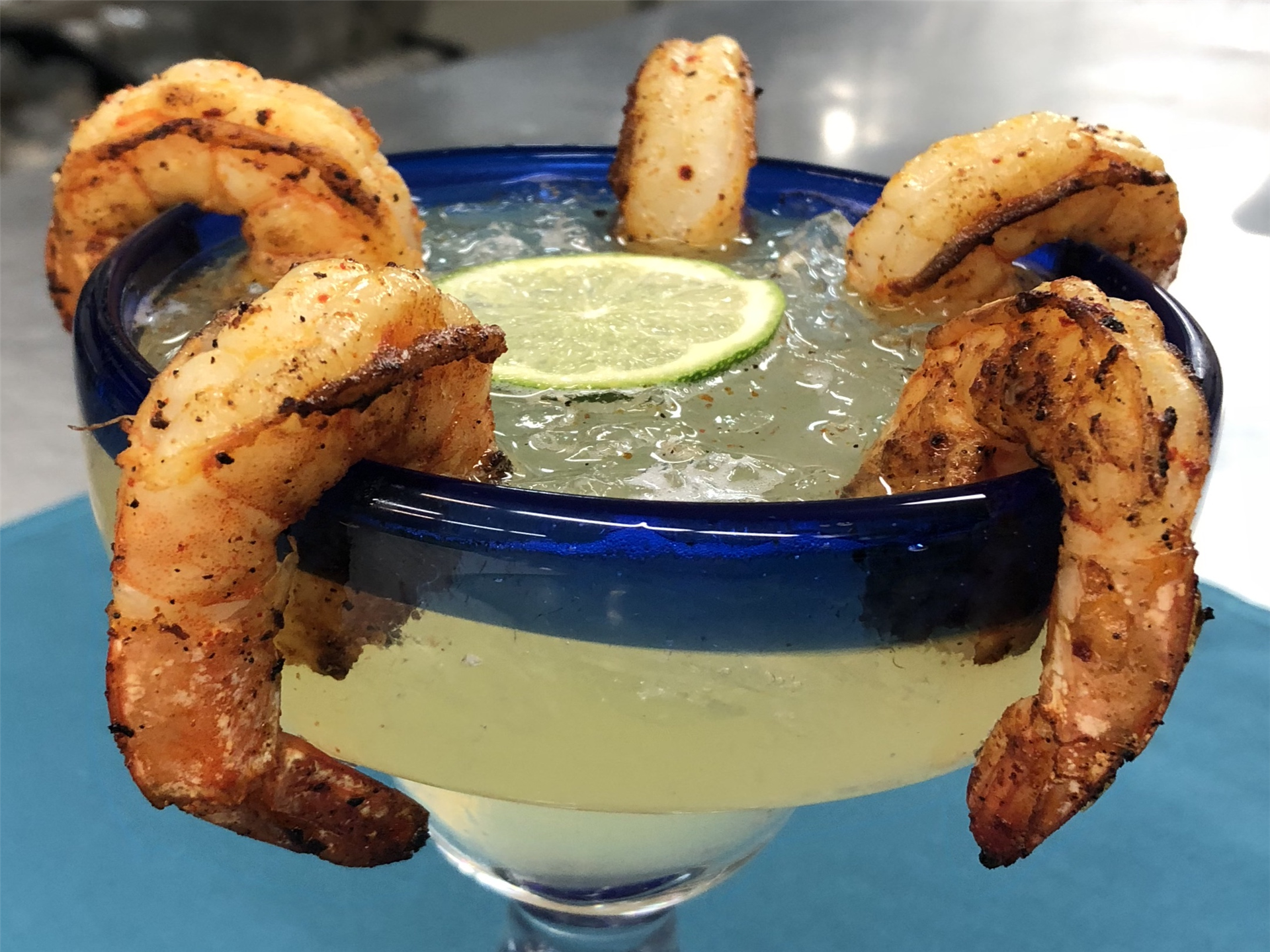 martini with several shrimp on the glass rim