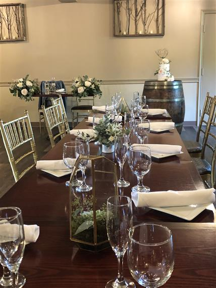 Rectagular table set with glasses and napkins with small flower arrangements