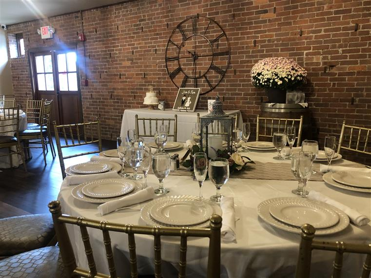 Wedding reception room. Round Tables with linens, set with plates and glasses. Flowers, wedding cake, photo of a couple and large iron clock decorate brick walls