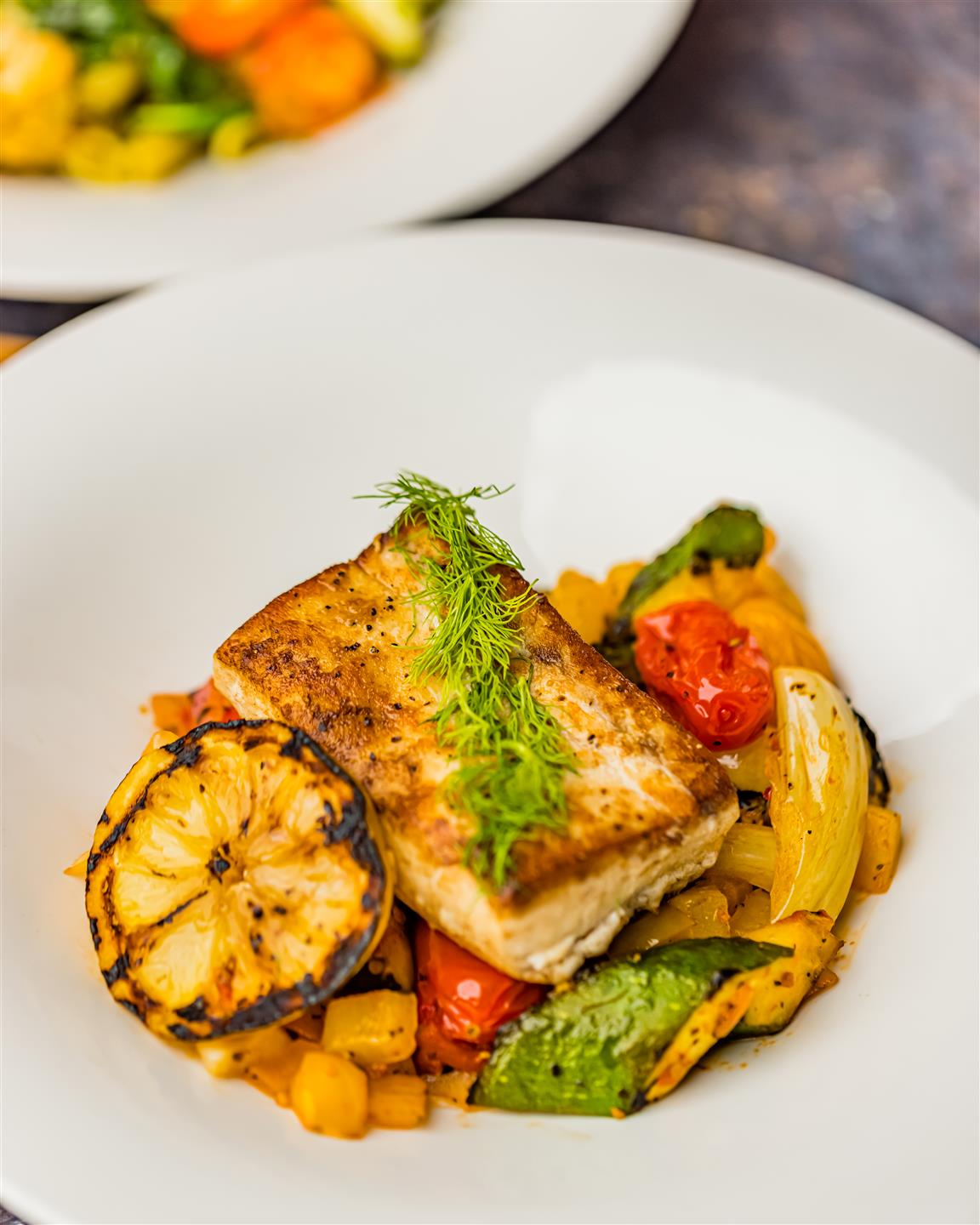 Fish on a plate with mixed veggies underneath and a half sliced lemon