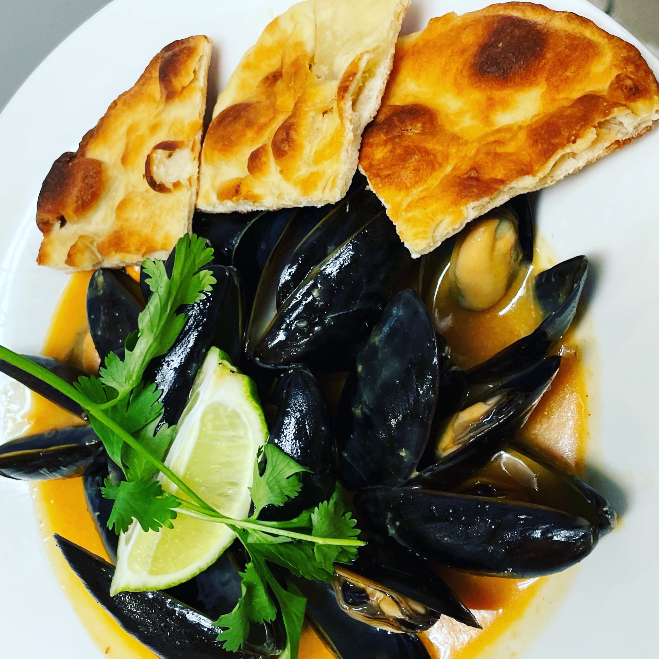 Mussels on a plate with sauce over top
