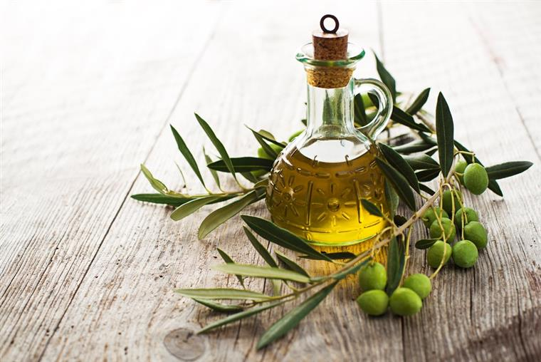Bottle of olive oil next to an olive branch with olives