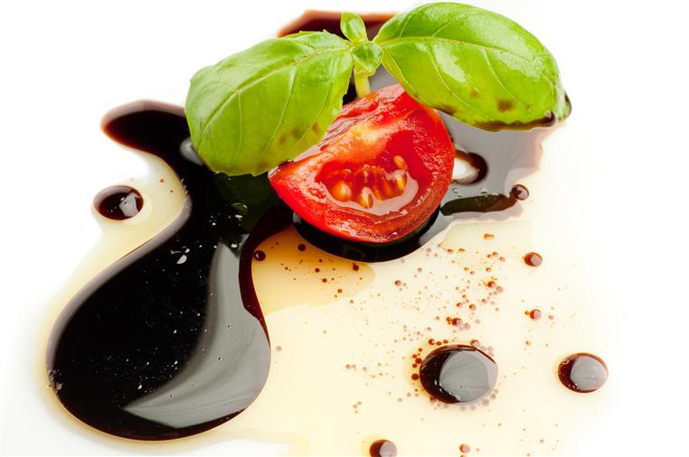 traditional balsamic drizzled on a plate with a small sliced tomato and basil leaf