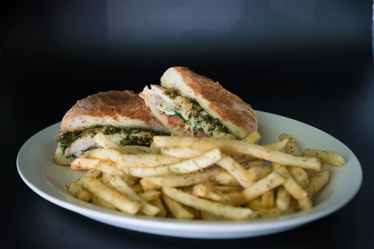a chicken panini with pesto sauce and tomatoes with a side of garlic fries