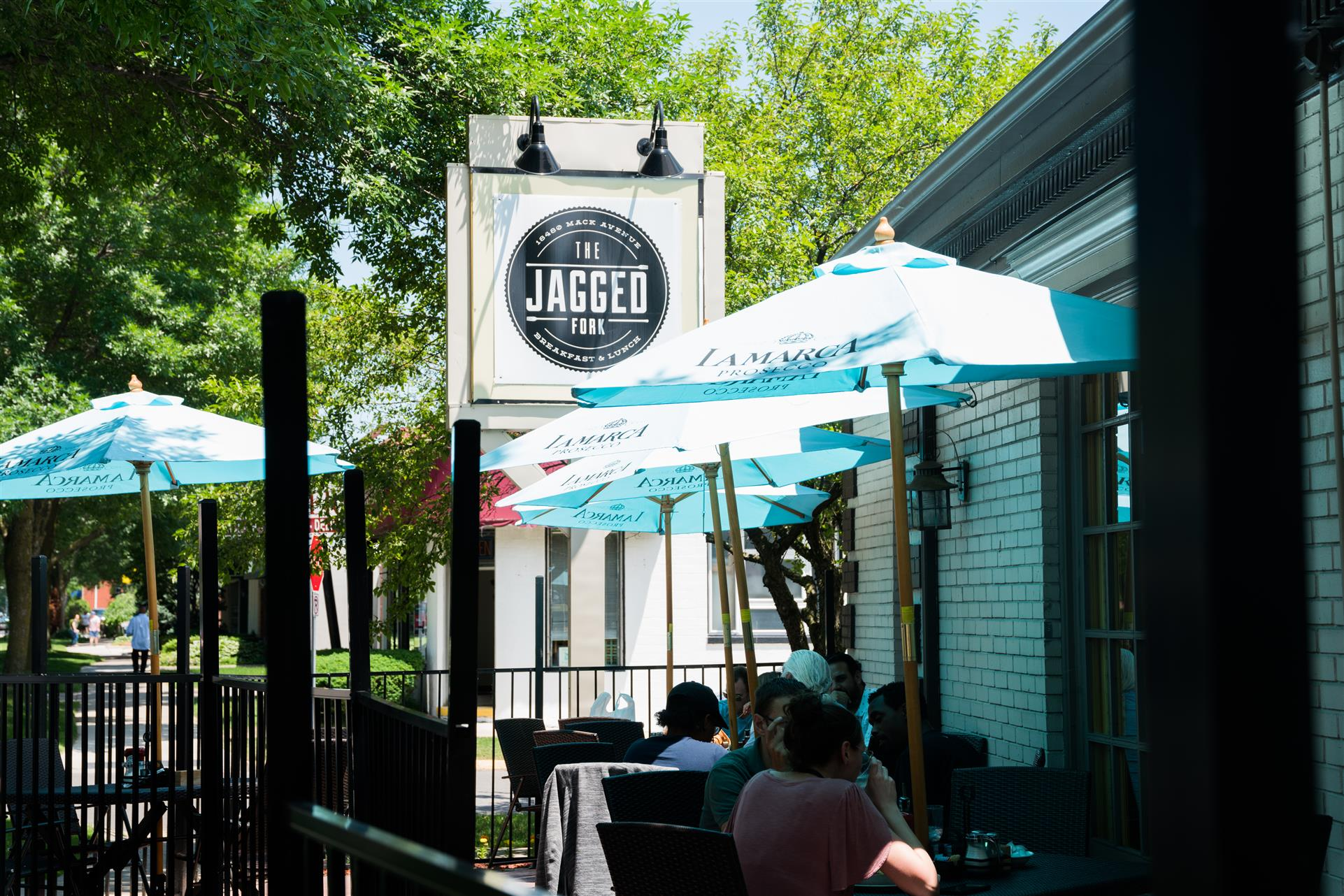 The Jagged Fork sign in front of customers sitting at tables outside under blue umbrellas