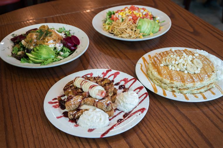 four plates of food: one of cobb salad, another of a salad with beets, another of french toast with raspberry drizzle and banana slices and another of pancakes with caramel drizzle and banana slices