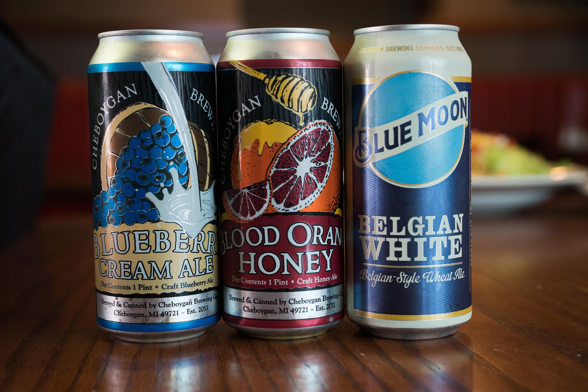 three beer cans: blueberry cream ale, blood orange honey ale, and blue moon belgian white