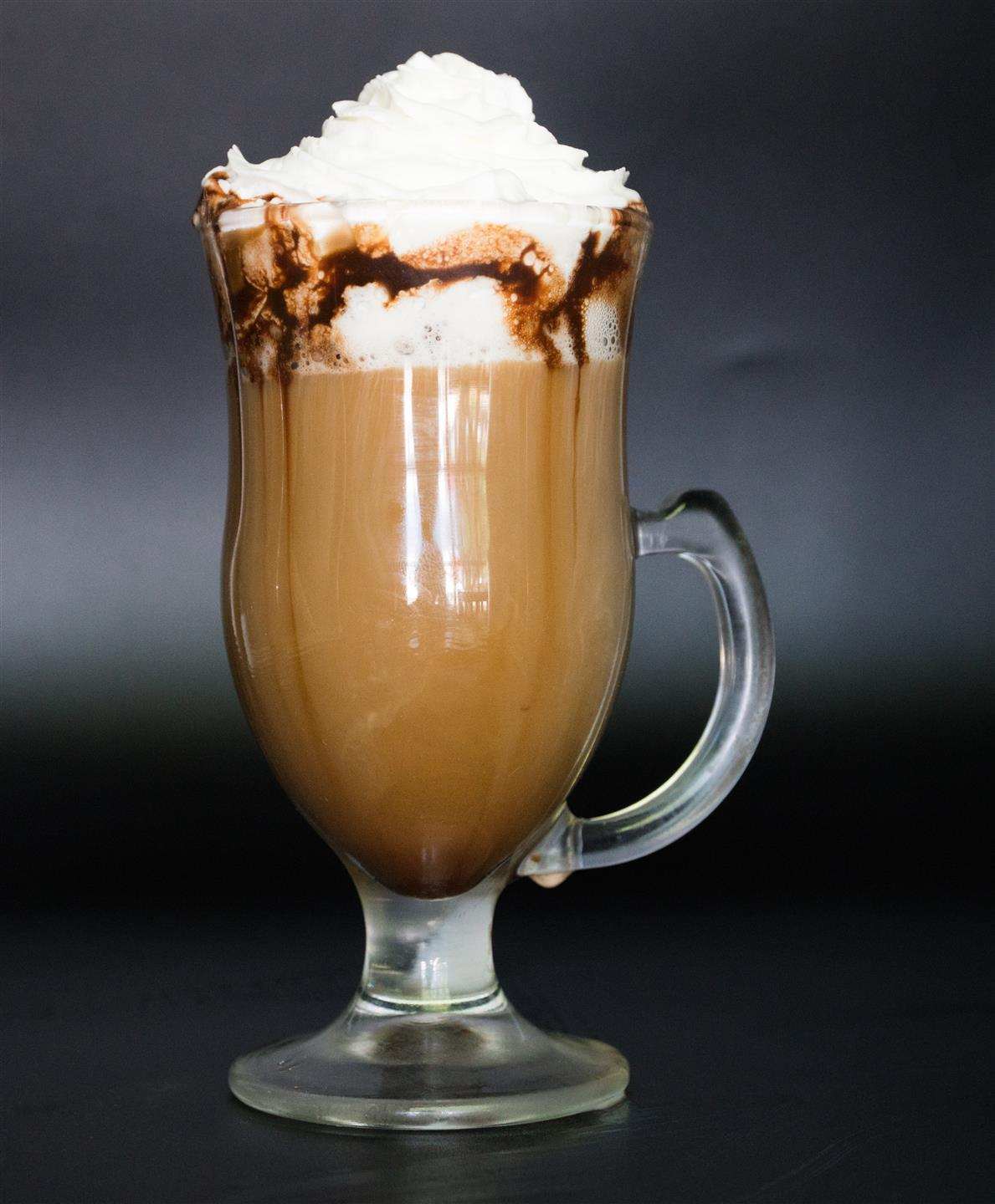 a cappucino in a glass mug with whipped cream