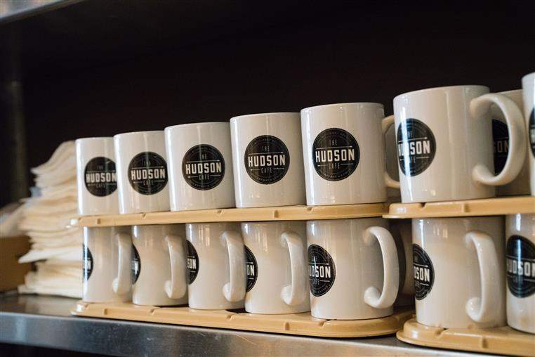 stacks of coffee mugs with the hudson cafe logo on them.
