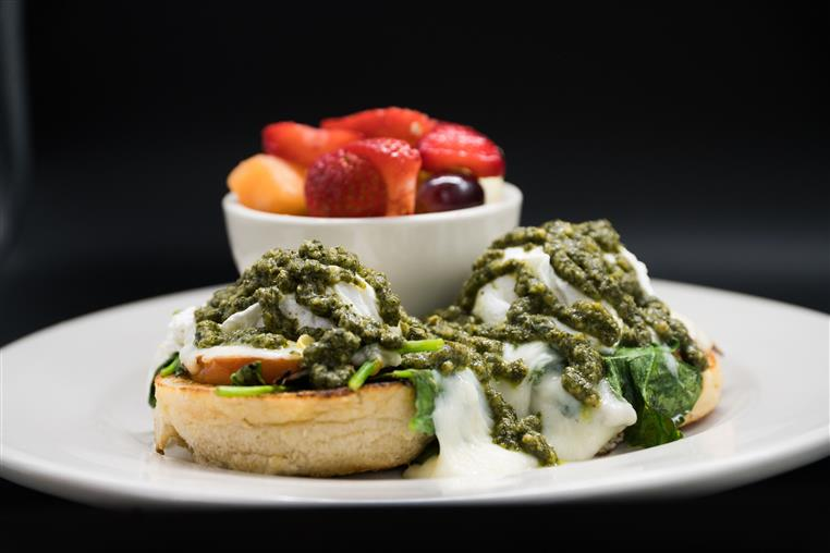 Pesto Benny. Grilled English muffin, homemade basil pesto, sautéed spinach, mozzarella and tomato, topped with two poached eggs. fresh fruit salad on the side.
