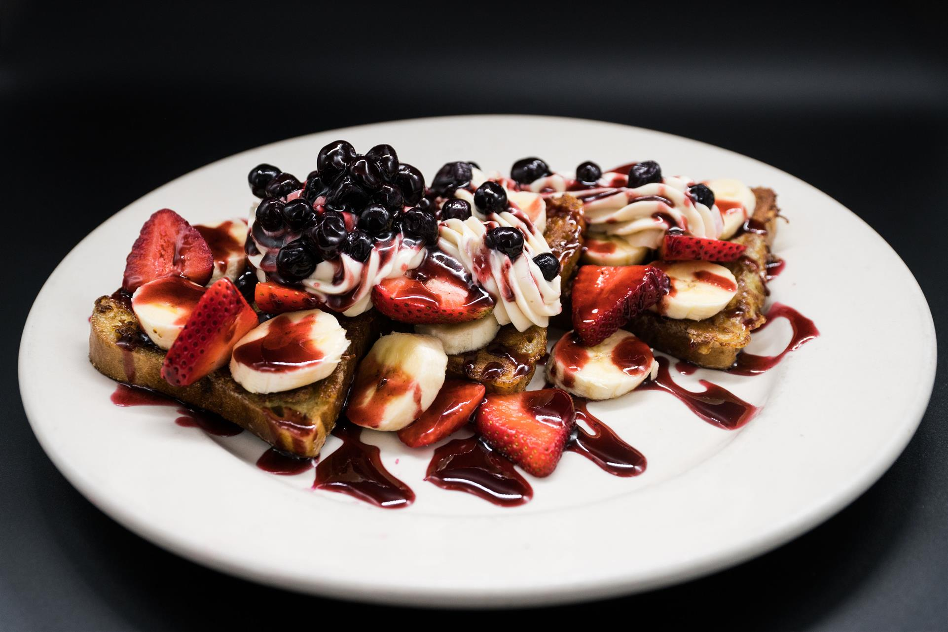 gluten free Very Berry French Toast. Stuffed with fresh sliced bananas and cream cheese frosting, topped with fresh berries and berry compote