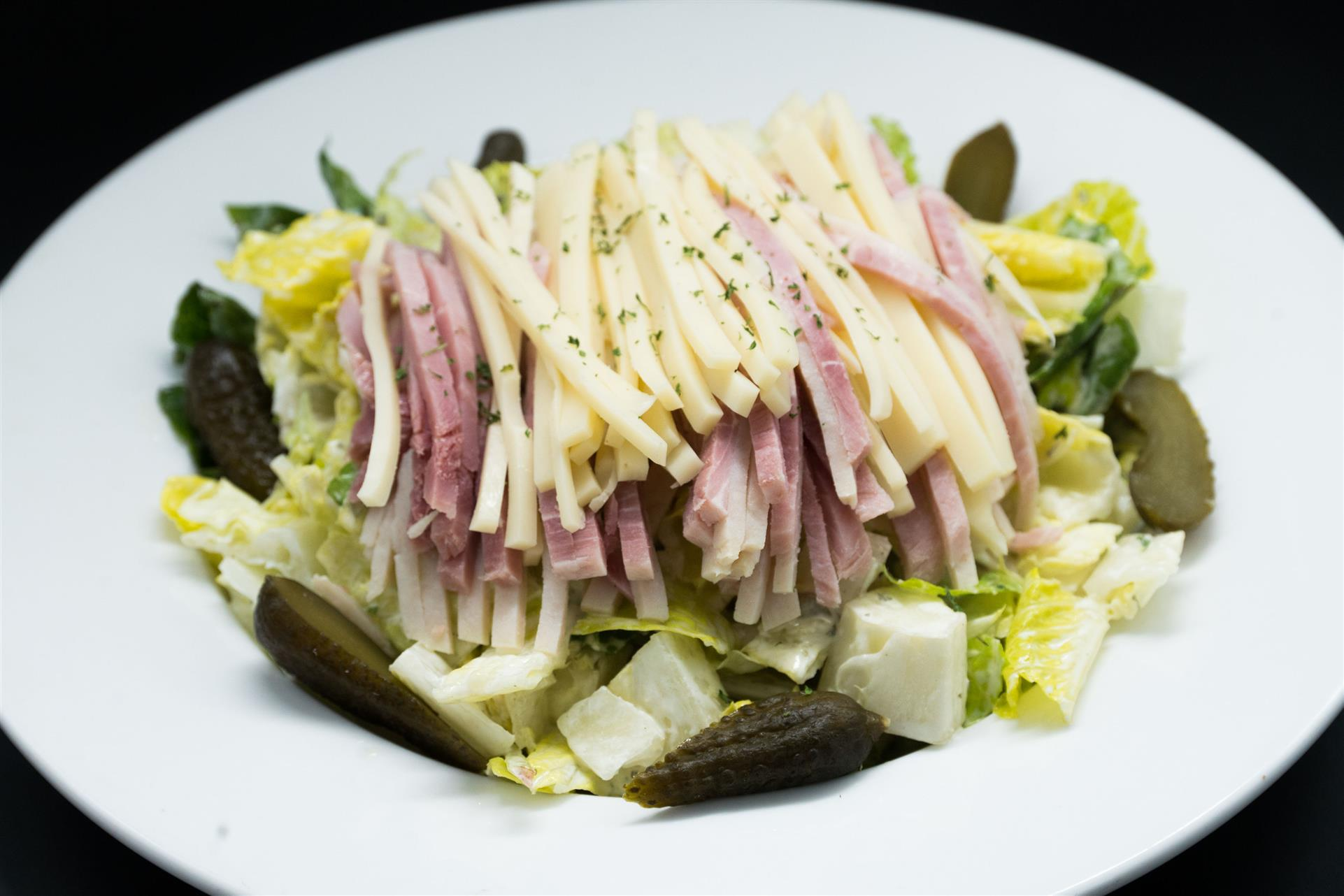 hudson salad. Smoked ham and turkey, romaine hearts, gherkin pickle, green olives and swiss in Hudson dressing