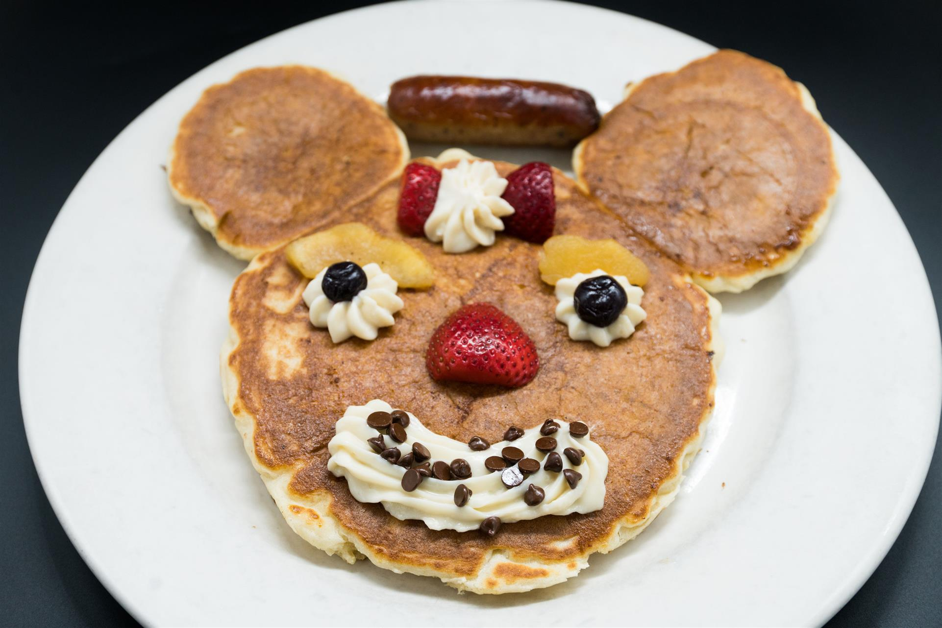 mickey mouse pancake with whipped cream and fresh strawberries.