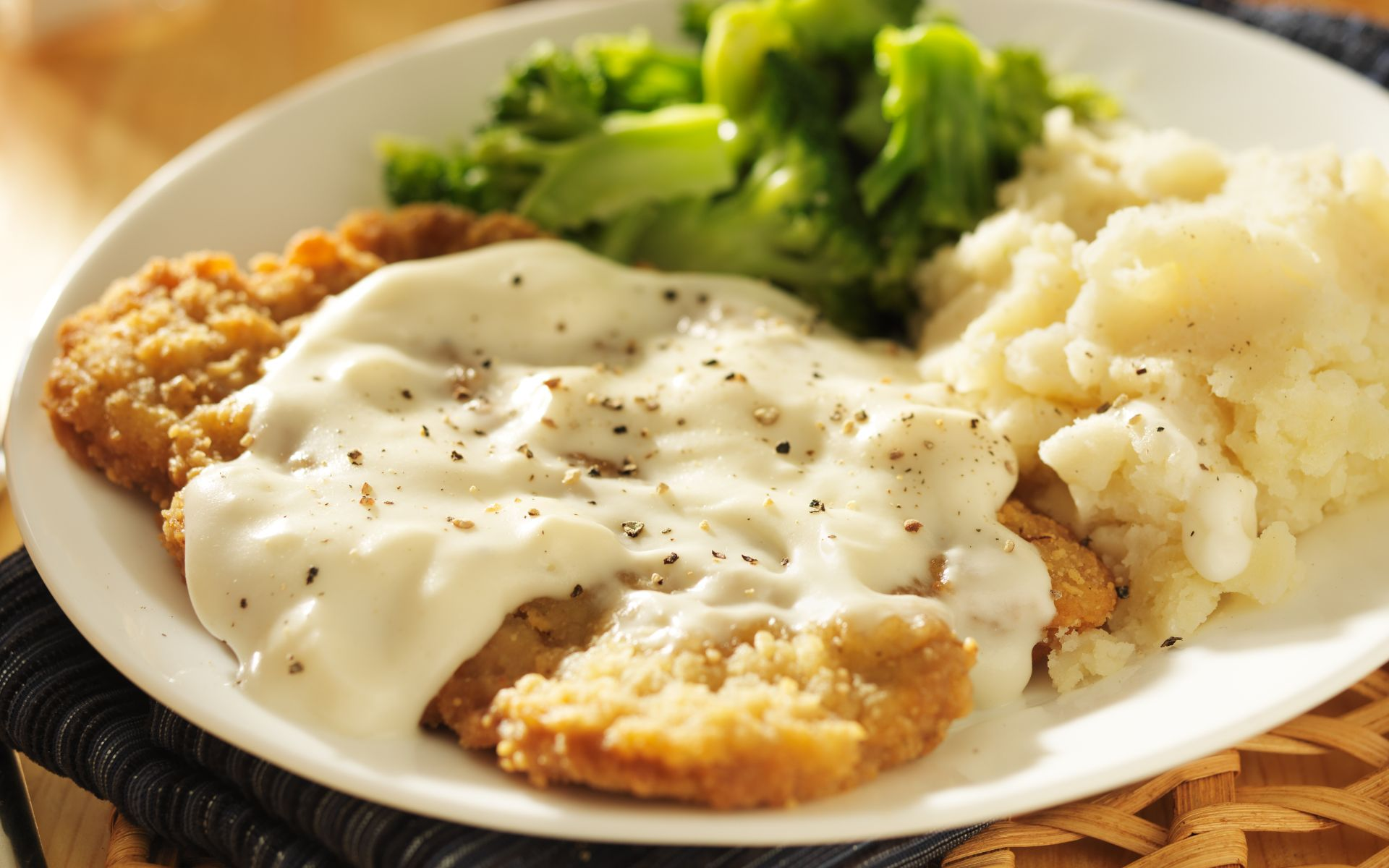 country fried steak with gravy, mashed potatoes and brocolli