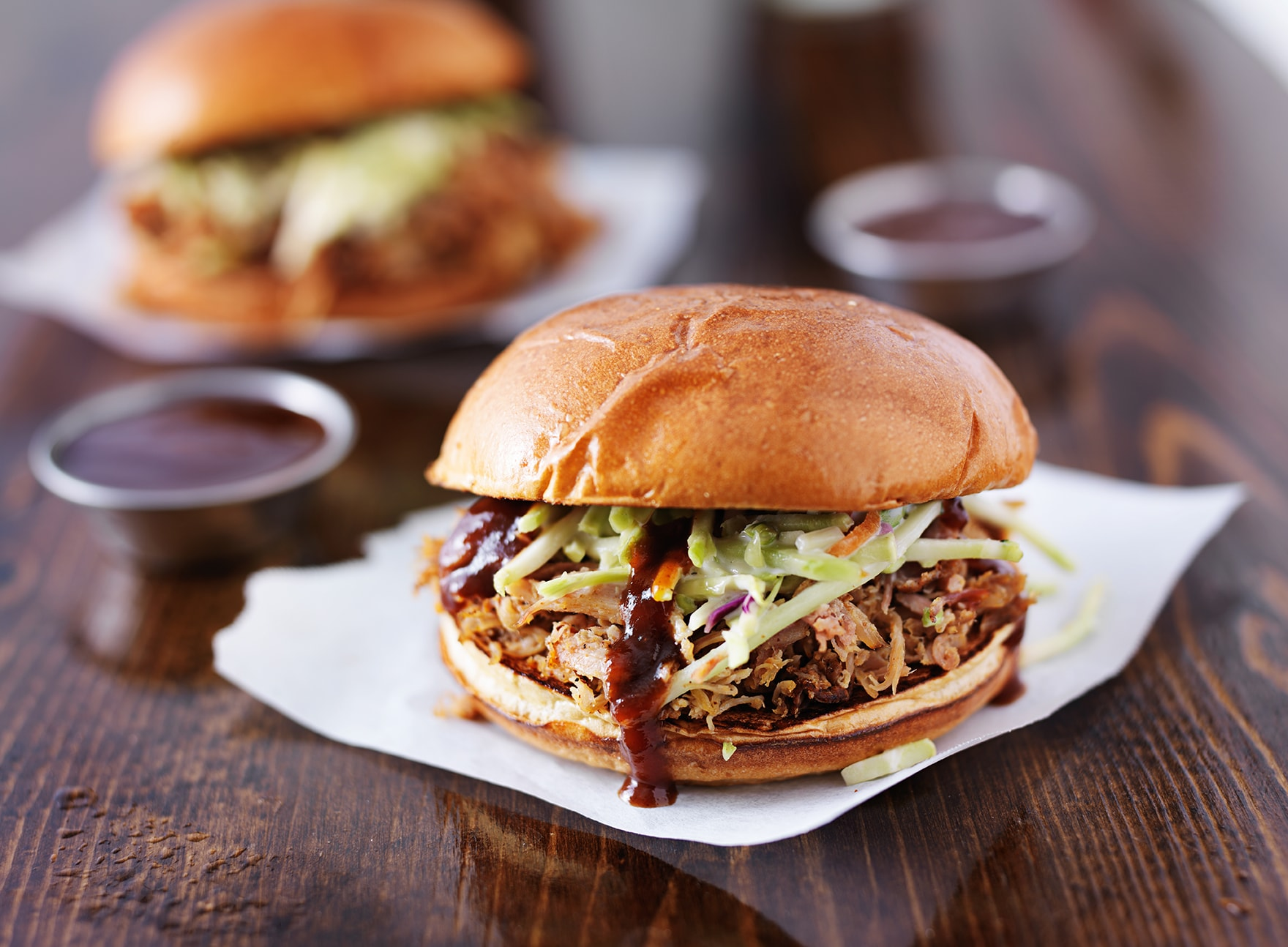 Pulled pork sandwiches with containers of BBQ sauce