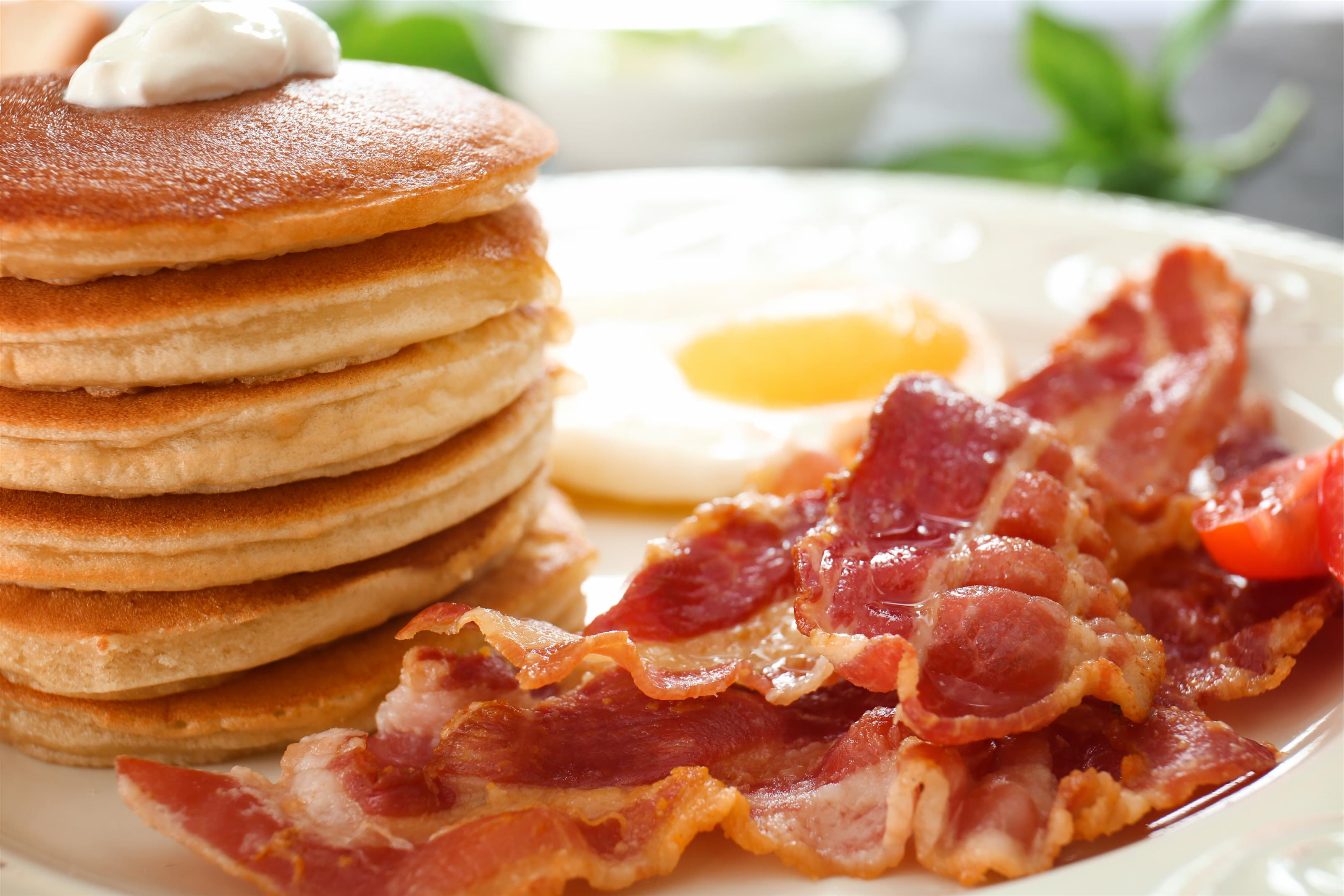 stack of pancakes topped with butter, eggs and bacon