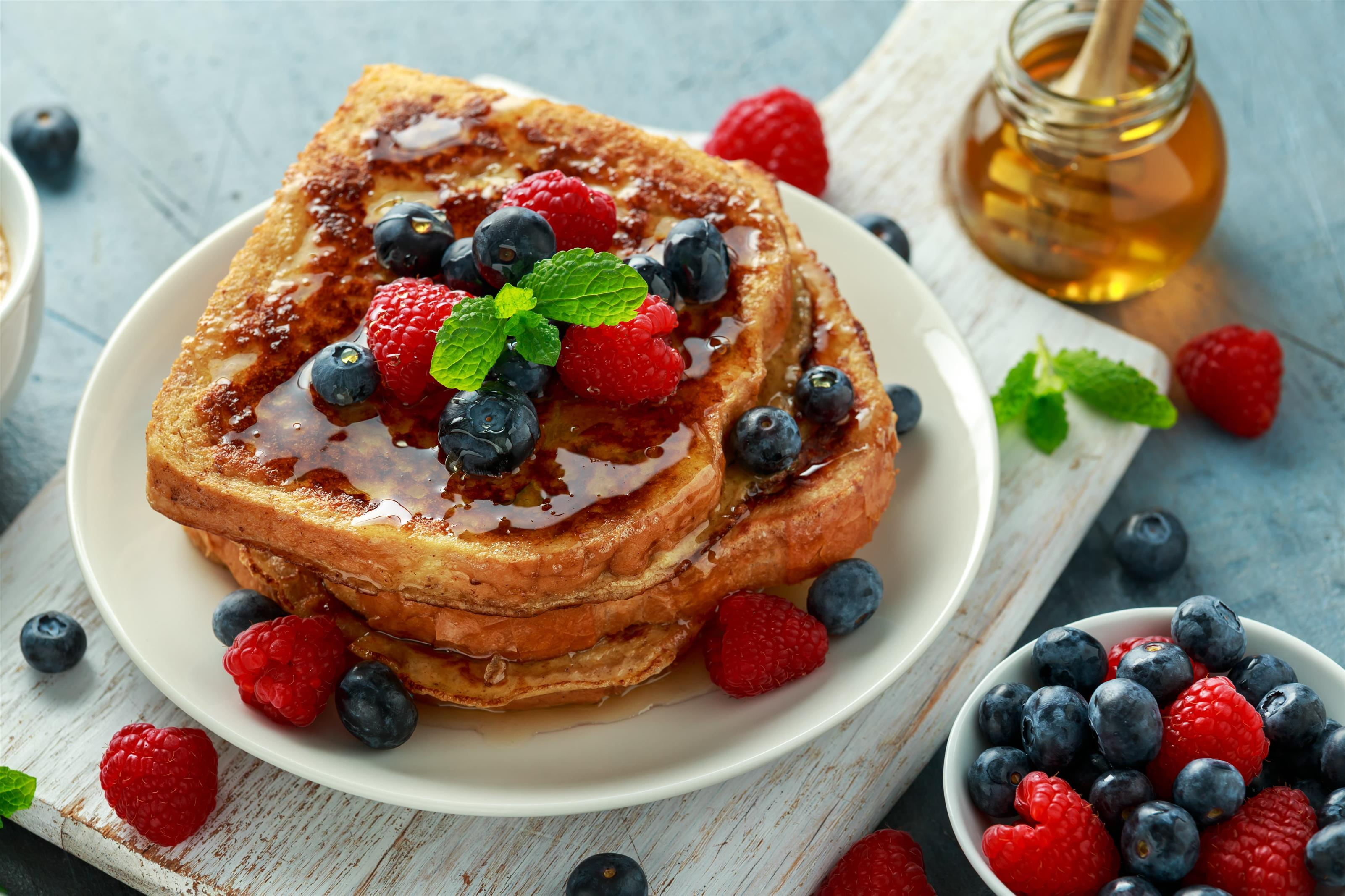 stack of pancakes topped with syrup, bananas, blueberries and strawberries