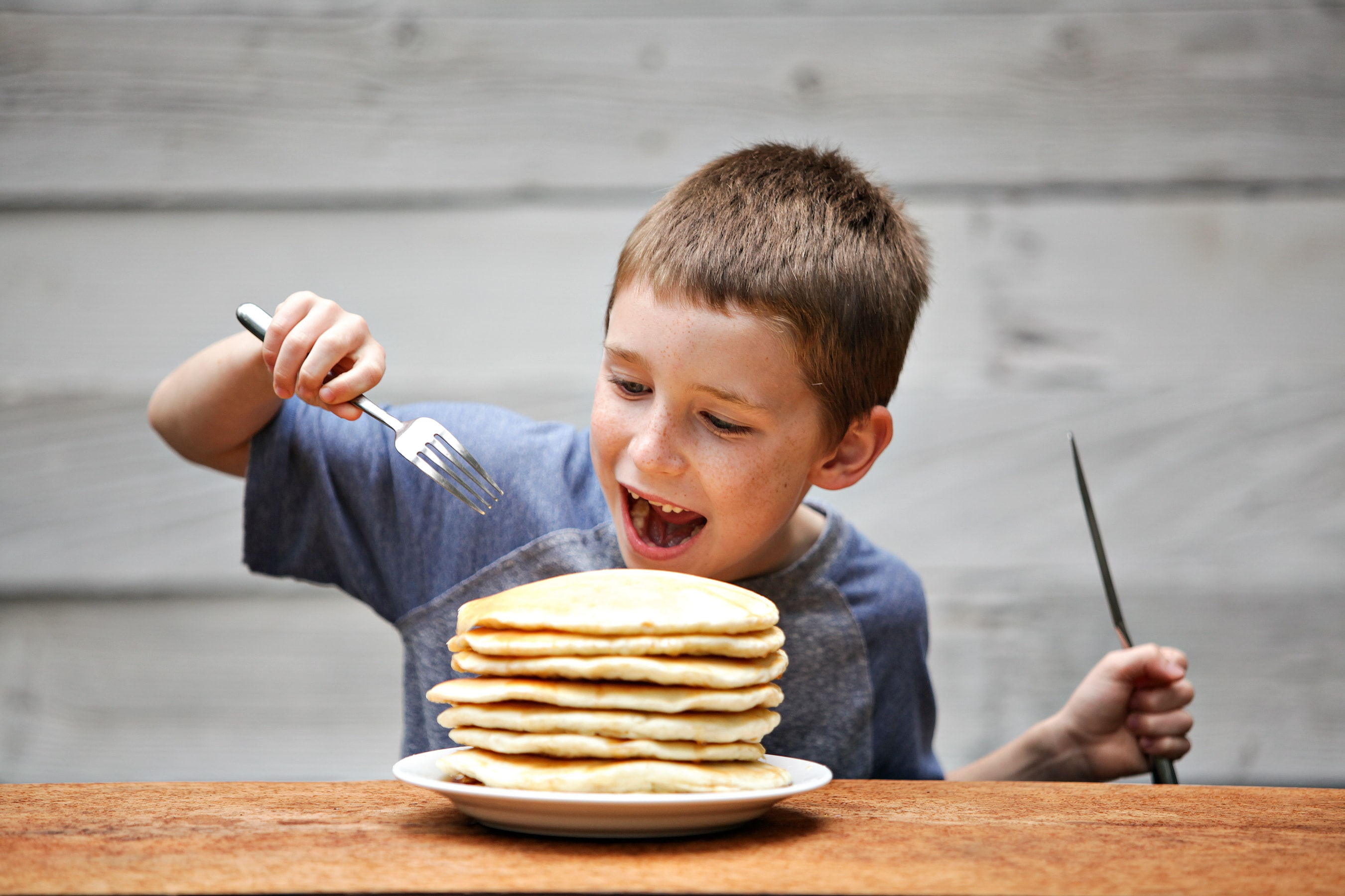 young boy smiling and about to eat a stack of pancakes