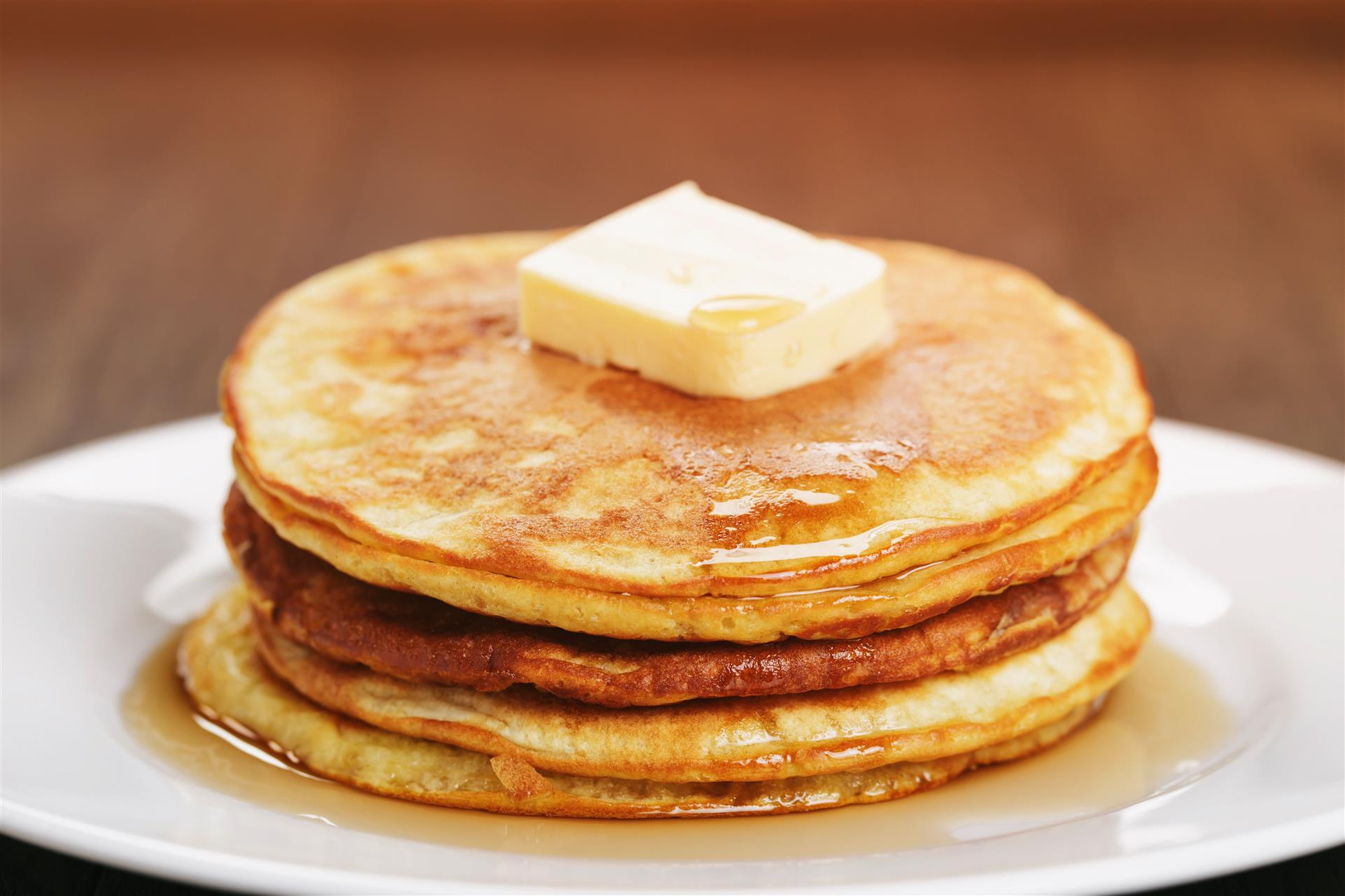stack of pancakes topped with butter and syrup