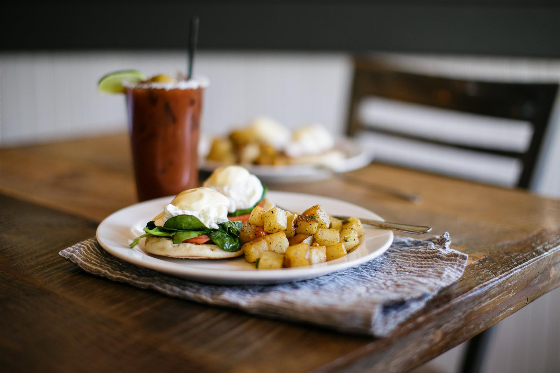 roasted potatoes and eggs benedict on a plate, with a drink and another plate of food in the background
